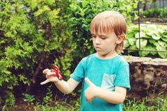 Muchacho lindo que juega con el tri hilandero de la mano de la persona agitada al aire libre Juguete de moda para las manos para  Foto de archivo libre de regalías