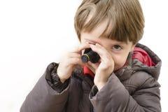 Muchacho lindo que juega con la cámara miniatura Imagen de archivo