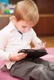 Muchacho lindo que juega con la tablilla Fotos de archivo