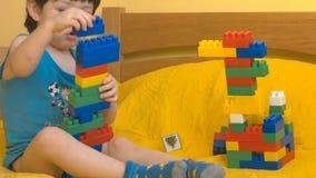 Muchacho lindo que juega con los bloques del juguete almacen de metraje de vídeo