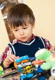 Muchacho lindo que juega con los juguetes foto de archivo