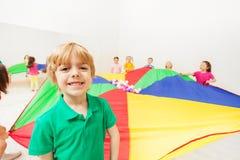 Muchacho lindo que juega el paracaídas del arco iris con los amigos Fotos de archivo