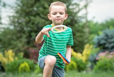 Muchacho lindo que juega los anillos que lanzan de un juego al aire libre en parque del verano La alegr?a de la victoria imagenes de archivo