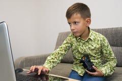 Muchacho lindo que juega a los videojuegos en casa Foto de archivo libre de regalías