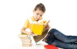 Muchacho lindo que lee un libro en el suelo Imagenes de archivo