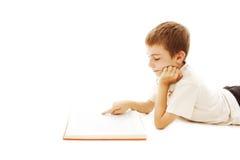 Muchacho lindo que lee un libro en el suelo Imagen de archivo libre de regalías