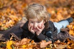 Muchacho lindo que miente en hojas de otoño Fotos de archivo