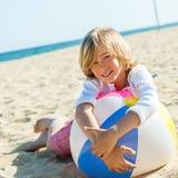 Muchacho lindo que pone en la pelota de playa. Imagenes de archivo