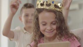 Muchacho lindo que pone la corona en la cabeza de la muchacha rizada adorable que mira en el espejo Muchacho galante que cuida pa almacen de video
