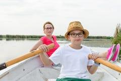 Muchacho lindo que se bate con la madre en barco Muchacho feliz activo que tiene f fotografía de archivo libre de regalías
