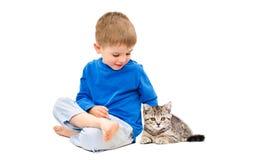 Muchacho lindo que se sienta con un recto escocés del gatito Imagen de archivo
