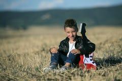 Muchacho lindo que se sienta en el campo con una guitarra Fotografía de archivo libre de regalías