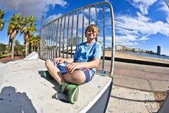Muchacho lindo que se sienta en el parque del patín Fotografía de archivo