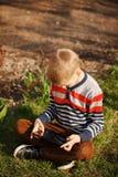 Muchacho lindo que se sienta en hierba en parque y que juega con la tableta fotos de archivo
