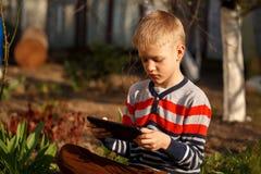 Muchacho lindo que se sienta en hierba en parque y que juega con la tableta Imagen de archivo libre de regalías