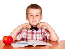 Muchacho lindo que se sienta en la tabla sobre el libro de ejercicio, manzana aislada Foto de archivo libre de regalías