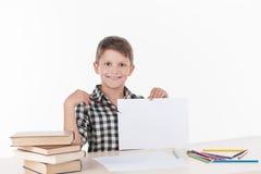 Muchacho lindo que se sienta en la tabla y la escritura Imágenes de archivo libres de regalías