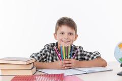 Muchacho lindo que se sienta en la tabla y que sostiene los lápices coloridos imagen de archivo