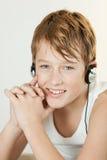 Muchacho lindo que sonríe mientras que escucha los auriculares Foto de archivo libre de regalías