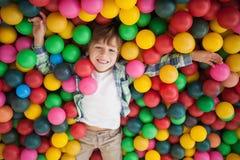 Muchacho lindo que sonríe en piscina de la bola Imágenes de archivo libres de regalías