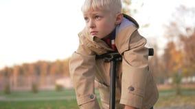 Muchacho lindo rubio con los ojos azules que miran cuidadosamente en la distancia metrajes