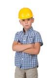 Muchacho lindo serio en la camisa a cuadros azul, vaqueros grises y el casco amarillo del edificio, aislados en el fondo blanco Imagenes de archivo
