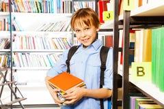 Muchacho lindo sonriente con los libros en biblioteca escolar Fotografía de archivo
