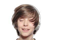 Muchacho lindo sonriente del adolescente con los auriculares Fotos de archivo