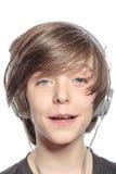Muchacho lindo sonriente del adolescente con los auriculares Foto de archivo libre de regalías