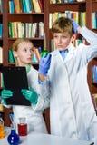Muchacho lindo y muchacha que hacen la investigación de la bioquímica adentro Imagen de archivo