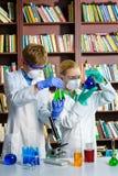 Muchacho lindo y muchacha que hacen la investigación de la bioquímica adentro Foto de archivo libre de regalías