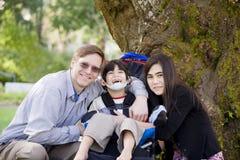 Muchacho lisiado en el sillón de ruedas rodeado por la familia Imagen de archivo libre de regalías