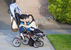 Muchacho lisiado en sillón de ruedas y su hermana Foto de archivo
