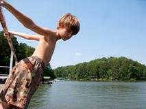 Muchacho listo para zambullirse en el lago Fotografía de archivo