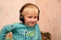 Muchacho littening a la música en auriculares Imagenes de archivo
