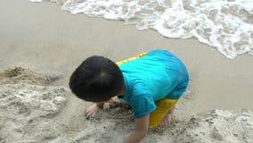 muchacho malasio del melayu de Asia que juega la arena en una playa almacen de metraje de vídeo
