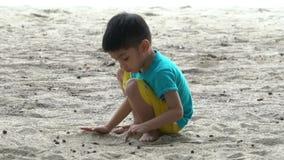 muchacho malasio del melayu de Asia que juega la arena en una playa metrajes