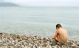 Muchacho, mar y guijarro Foto de archivo libre de regalías
