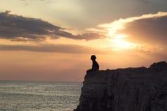 Muchacho misterioso que se sienta en el precipicio de un acantilado Imagen de archivo