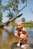 Muchacho mojado feliz que se sienta en roca en el lago Imagen de archivo