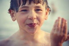 Muchacho mojado que limpia el agua de la cara Foto de archivo libre de regalías