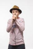 Muchacho moreno del adolescente del cantante en un jersey rosado en sombrero del oro con un micrófono Foto de archivo