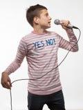 Muchacho moreno del cantante en un puente rosado con un micrófono Imagen de archivo