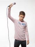 Muchacho moreno del cantante en un puente rosado con un micrófono Fotografía de archivo libre de regalías