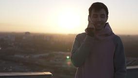 Muchacho moreno en la situación casual en el tejado en llamaradas de la lente y llamada usando su smartphone El hablar, sonriendo almacen de metraje de vídeo