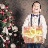 Muchacho multiraceal divertido que sostiene una caja de regalo grande en la Navidad Foto de archivo