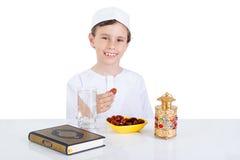 Muchacho musulmán joven que lleva a cabo fechas listas para el brakfast en el Ramadán Imágenes de archivo libres de regalías