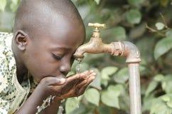 Muchacho negro africano que bebe el agua potable fresca imagen de archivo