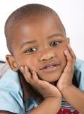 Muchacho negro de tres años que miente abajo sonriendo Fotografía de archivo libre de regalías