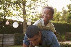 Muchacho negro joven que juega en su parte posterior del ½ s del ¿del dadï en un jardín Imágenes de archivo libres de regalías